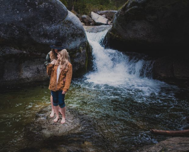 Engagement photography in Sequoia National Park of a stylish, adventurous couple posing on a rock in the middle of a creek wtih a waterfall in the background.