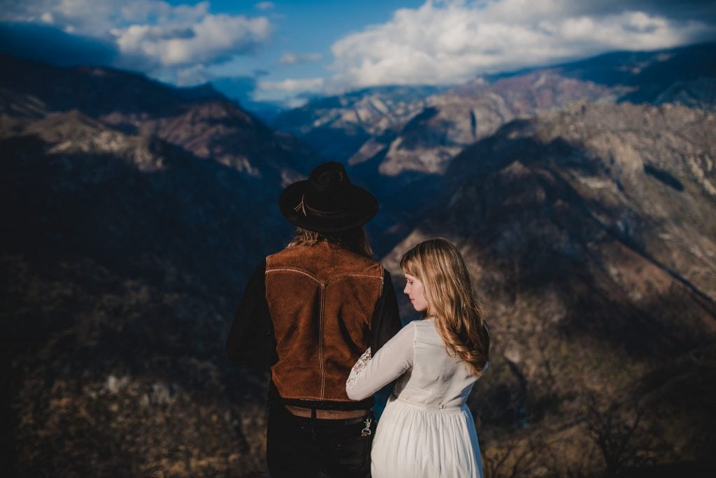 Adventurous wedding photography in Sequoia National Park of a bride and groom posing for their portraits overlooking the Sierra Nevada mountains in California.
