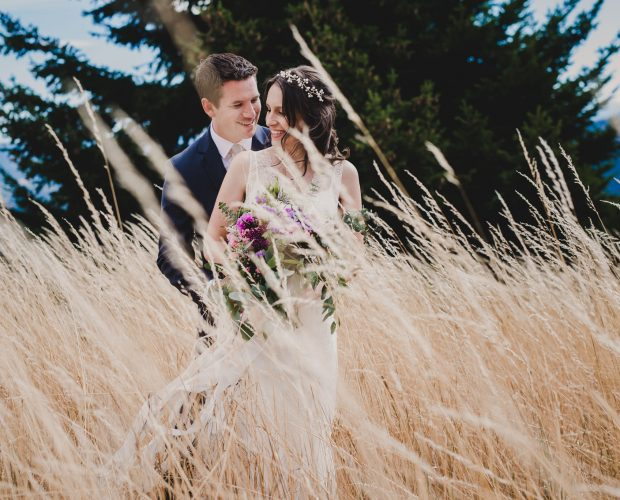A couple embraces on their wedding day in a field of wheat at Gorge Crest Vineyards.