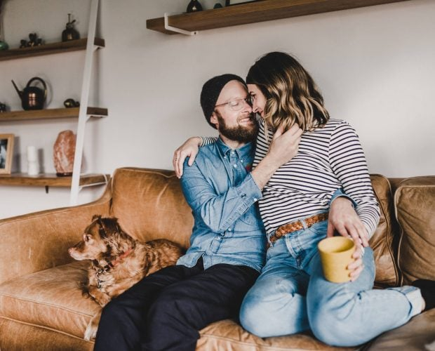 During their lifestyle engagement session, A couple cuddles on the couch with their dog.