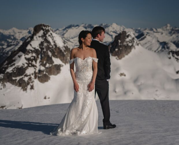 Bride and Groom Standing on Snowy Mountain top back-to-back