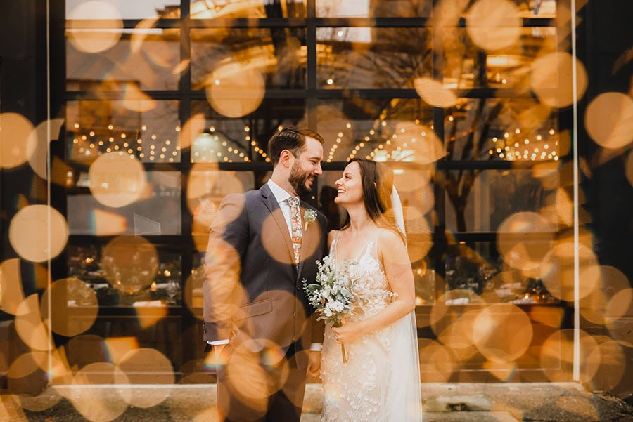 A double exposure portrait of a bride and groom and twinkling lights.