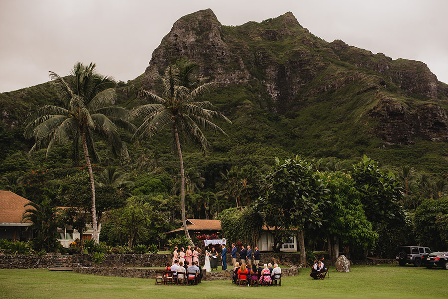 A small wedding ceremony on Oahu, Hawaii with palm trees and mountains in the background.