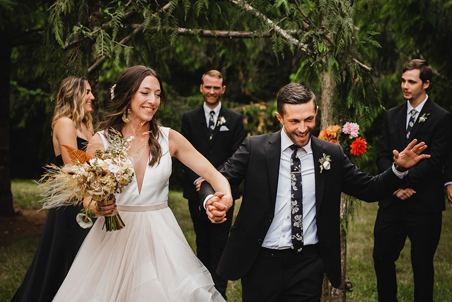 A bride and groom celebrate during their wedding ceremony while walking back up the aisle as husband and wife.