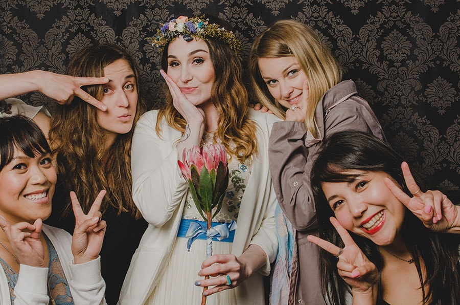 bride on her wedding day posing in a photo booth with her friends.