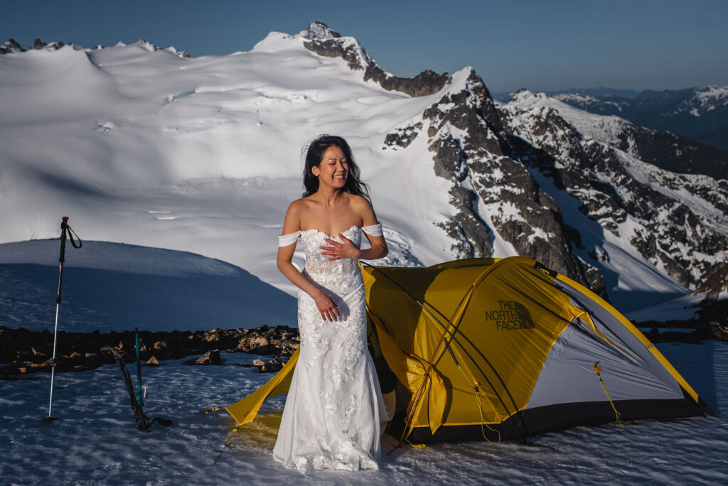 Bride emerging from tent on snowy mountain top