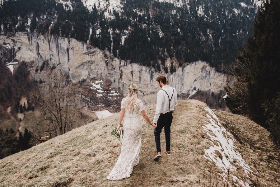 Bride and Groom holding hands overlooking the alps in Switzerland