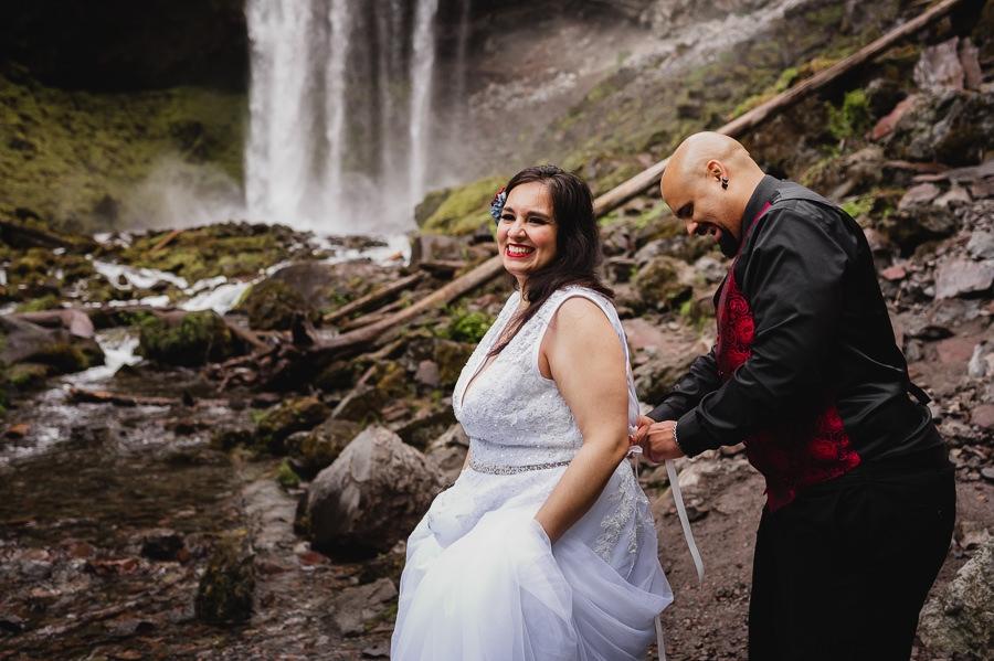 Groom buttoning bride's wedding dress