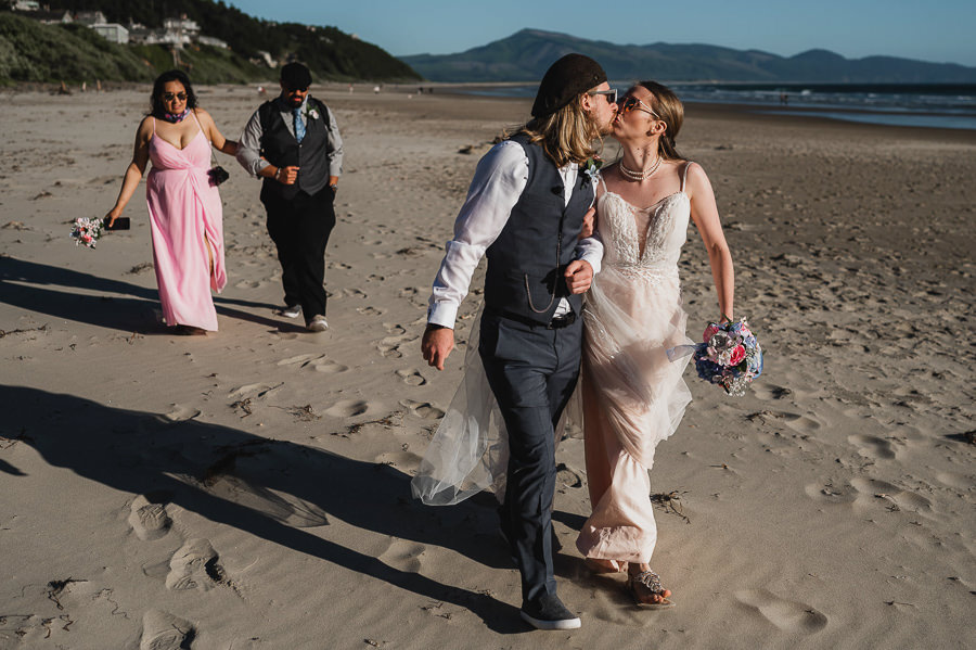 Bride and groom on beach with wedding party