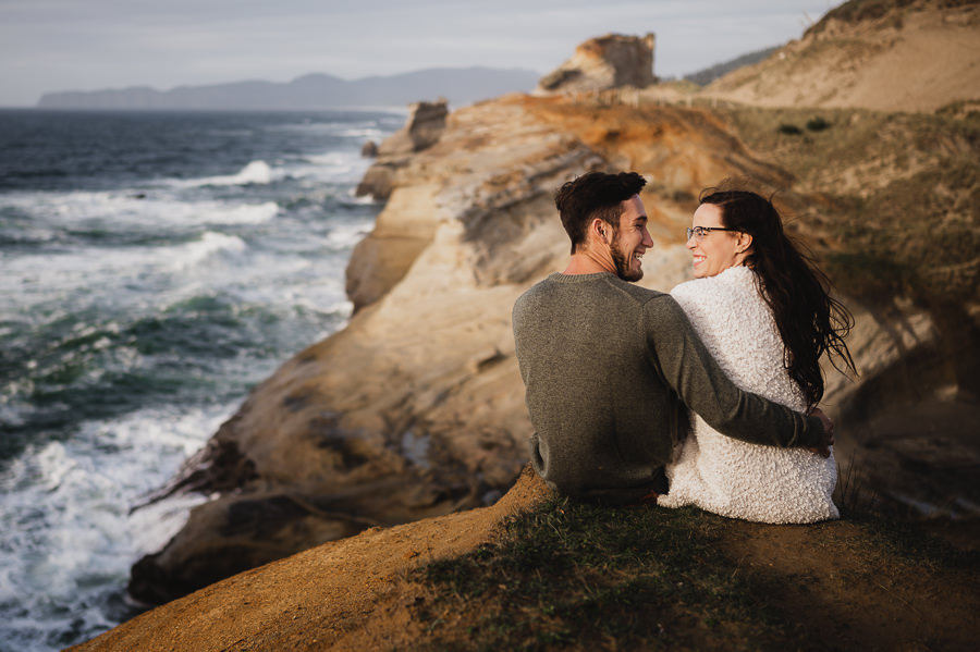 Couple smiling at each other over looking the Oregon Coast