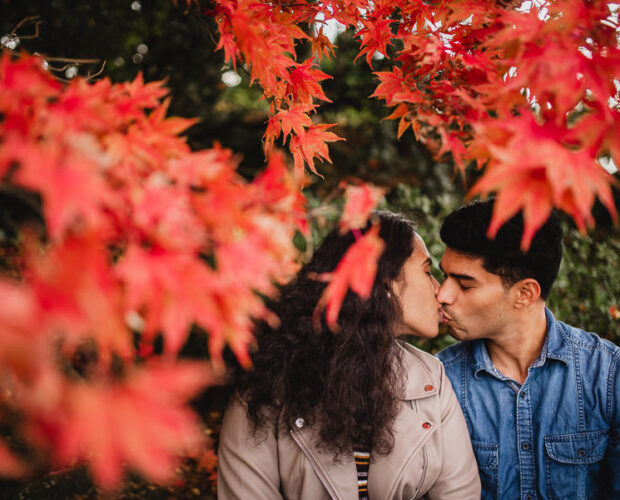 Couple kissing with bright autumn leaves